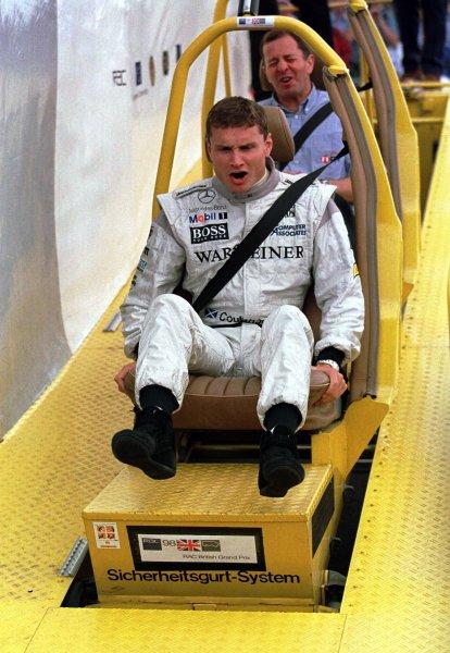 1998 British Grand Prix.Silverstone, England.10-12 July 1998.David Coulthard (McLaren Mercedes-Benz) and Martin Brundle (ITV television comentator) try the crash test dummy impact machine.World Copyright - Steve Etherington/LAT Photographic