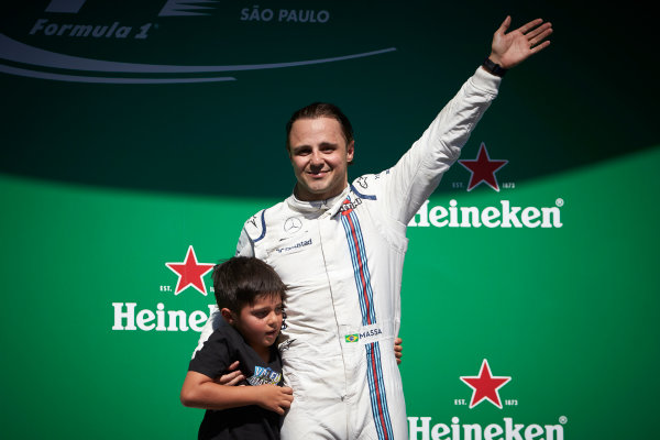 Interlagos, Sao Paulo, Brazil. Sunday 12 November 2017. Felipe Massa, Williams Martini Racing, with his son Felipinho waves to his home fans from the podium after his final home race. World Copyright: Steve Etherington/LAT Images  ref: Digital Image SNE17587