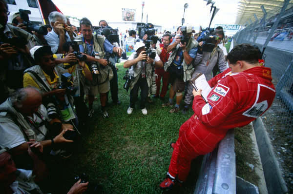 Sepang, Kuala Lumpur, Malaysia. 15-17 October 1999. Michael Schumacher (Ferrari F399) studies a telemetry readout on the grid before the race, surrounded by photographers. Ref: 99MAL08. World Copyright - LAT Photographic