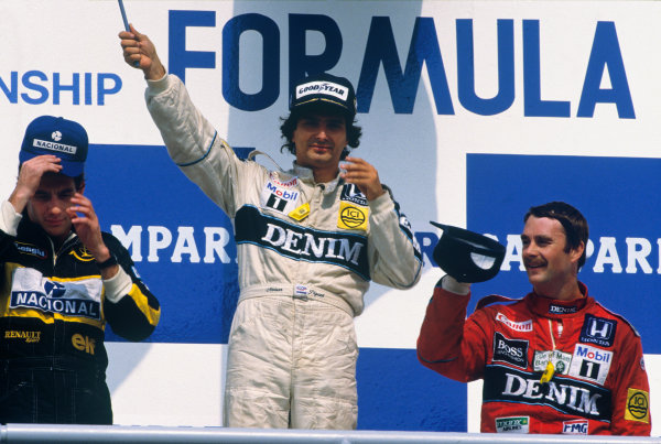 Hockenheim, Germany. 25-27 July 1986. Nelson Piquet (Williams FW11 Honda) 1st position, Ayrton Senna (Lotus 98T Renault) 2nd position, and Nigel Mansell (Williams FW11 Honda) 3rd position, on the podium. Portrait. Ref: 86 GER 18. World Copyright - LAT Photographic