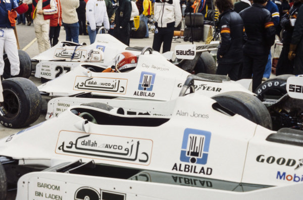 Alan Jones' Williams FW07 Ford with Clay Regazzoni already sat in his car in the pitlane.