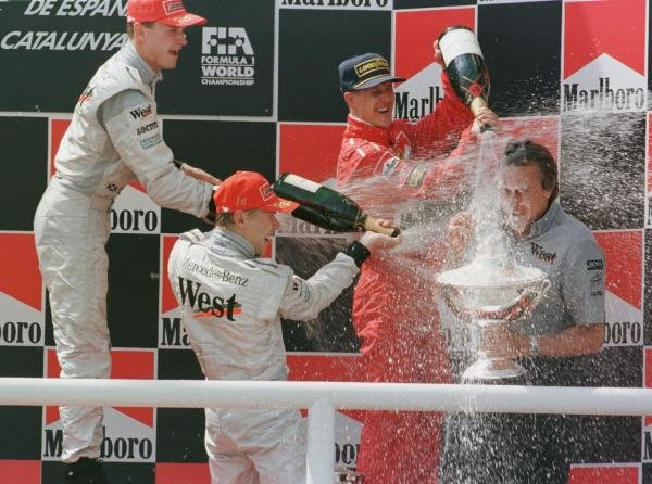 1998 Spanish Grand Prix.Catalunya, Barcelona, Spain.8-10 May 1998.Mika Hakkinen, David Coulthard (both McLaren Mercedes-Benz) and Michael Schumacher (Ferrari) spray champagne over McLaren-Mercedes-Benz team director Mansour Ojjeh after finishing in 1st, 2nd and 3rd positions respectively.World Copyright - Steve Etherington/LAT Photographic