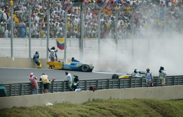 2003 Brazilian Grand Prix.  Interlagos, Sao Paulo, Brazil. 4-6 April 2003. Fernando Alonso (Renault) slumps hurt by the side of the track after his huge crash out of the last turn. World Copyright - Steve Etherington/LAT Photographic  ref: Digital Image Only