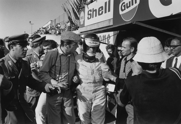 Monza, Italy. 8-10 September 1967. Jim Clark (Lotus 49 Ford), 3rd position, is led down the pit lane by photographer and journalist,  Bernard Cahier , portrait. World Copyright - LAT Photographic. ref: L67/717/2