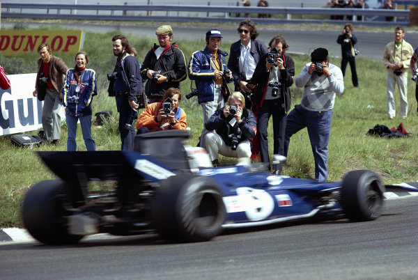 Photographers standing close to action, while Jackie Stewart, Tyrrell 003 Ford, passes by.