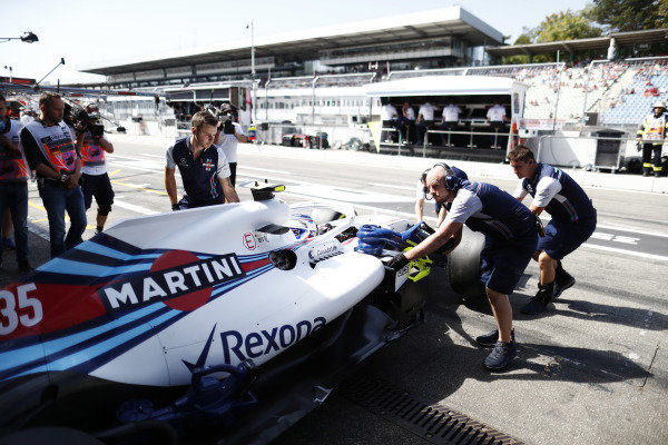 Mechanics push the Sergey Sirotkin Williams FW41 Mercedes into the garage.