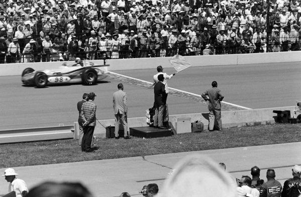A yellow flag is waved. Parnelli Jones, J. C. Agajanian, Watson Offenhauser, passes.