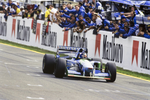Michael Schumacher, Benetton B194 Ford, punches the air in celebration as his team cheers him across the line.