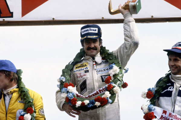 Clay Regazzoni celebrates victory on the podium with René Arnoux, 2nd position, and Jean-Pierre Jarier, 3rd position.