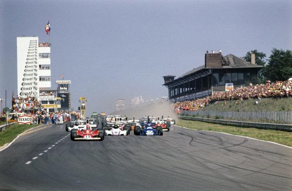 Pole sitter Niki Lauda, Ferrari 312T, leads the field away at the start. Carlos Pace, Brabham BT44B, follows, ahead of Patrick Depailler, Tyrrell 007.