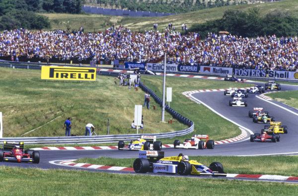 Nigel Mansell, Williams FW11B Honda, leads Gerhard Berger, Ferrari F1-87, Nelson Piquet, Williams FW11B Honda, Alain Prost, McLaren MP4-3 TAG, Michele Alboreto, Ferrari F1-87, Ayrton Senna, Lotus 99T Honda, Thierry Boutsen, Benetton B187 Ford and Stefan Johansson, McLaren MP4-3 TAG, on the opening lap.