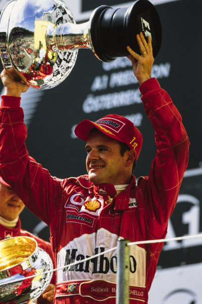 Rubens Barrichello, 2nd position, celebrates on the podium. He was given the winner's trophy by Michael Schumacher, 1st position.