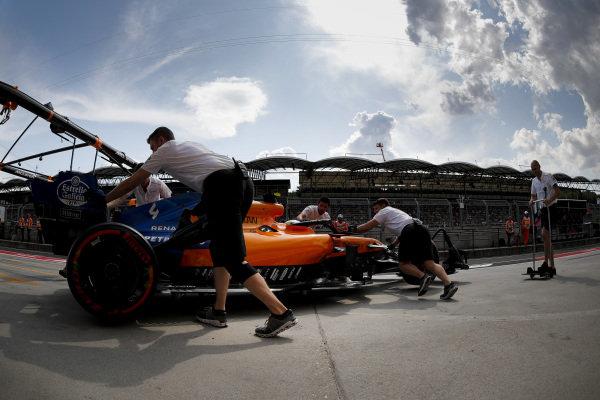 Lando Norris, McLaren MCL34, is returned to the garage