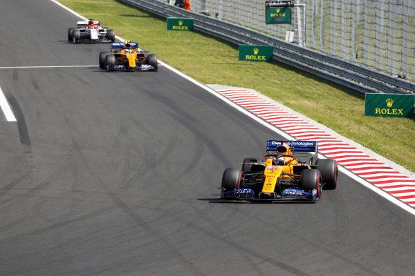 Carlos Sainz Jr., McLaren MCL34, leads Lando Norris, McLaren MCL34, and Kimi Raikkonen, Alfa Romeo Racing C38