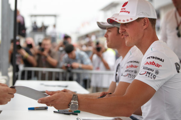 Hungaroring, Budapest, Hungary 26th July 2012 Michael Schumacher, Mercedes AMG and Nico Rosberg, Mercedes AMG, signs autographs for fans.  World Copyright: Steve Etherington/LAT Photographic ref: Digital Image FA4C6858 copy