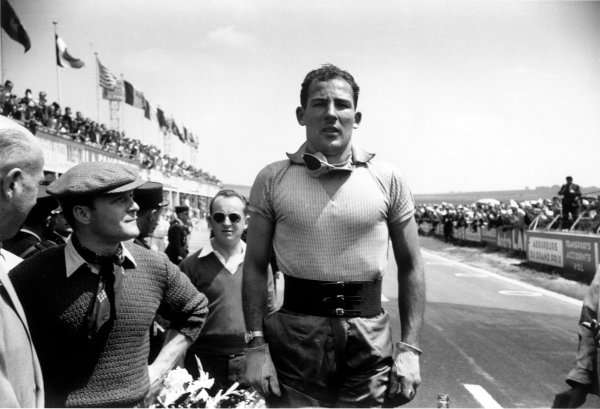 Reims, France. 4th - 5th July 1953. Stirling Moss (Jaguar C-Type), 1st position, stands to attention for the national anthem, portrait. World Copyright: LAT Photographic. Ref: 53/66 - 28A.