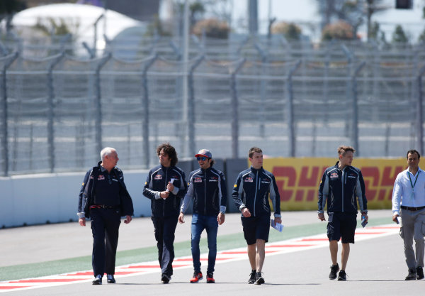 Sochi Autodrom, Sochi, Russia.  Thursday 28 April 2016. Carlos Sainz Jr, Toro Rosso, walks with team members, including former Manor boss John Booth in his first race with the team. World Copyright: Sam Bloxham/LAT Photographic ref: Digital Image _L4R6303