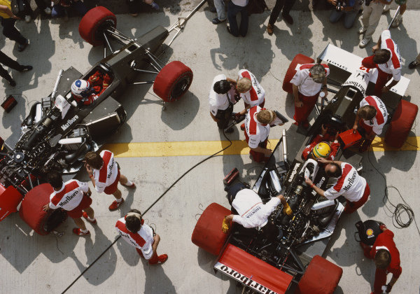 Ayrton Senna, McLaren MP4-4 Honda, with mechanics and engineers all around him as team mate Alain Prost looks over during practice.