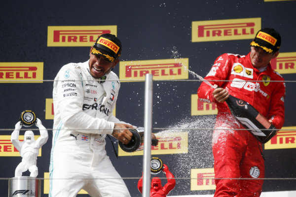 Lewis Hamilton, Mercedes AMG F1, 1st position, sprays Charles Leclerc, Ferrari, 3rd position, with Champagne on the podium