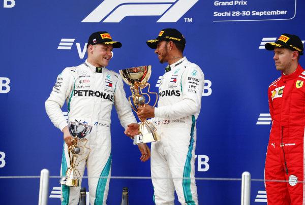 Valtteri Bottas, Mercedes AMG F1, 2nd position, and Lewis Hamilton, Mercedes AMG F1, 1st position, talk on the podium alongside Sebastian Vettel, Ferrari, 3rd position