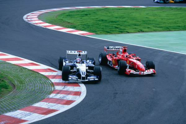 2004 Belgian Grand Prix.Spa Francorchamps, Belgium. 27th - 29th August.Juan Pablo Montoya, WilliamsF1 BMW FW26 overtakes Michael Schumacher, Ferrari F2004 going into the bus stop. Action. World Copyright:LAT PhotographicRef:35mm Image A10