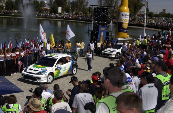The Fords of Francois Duval (BEL) and Markko Martin (EST) make their way onto the podium.World Rally Championship, Rd3, Rally Mexico, Leon, Mexico. Day Three. 14 March 2004.DIGITAL IMAGE