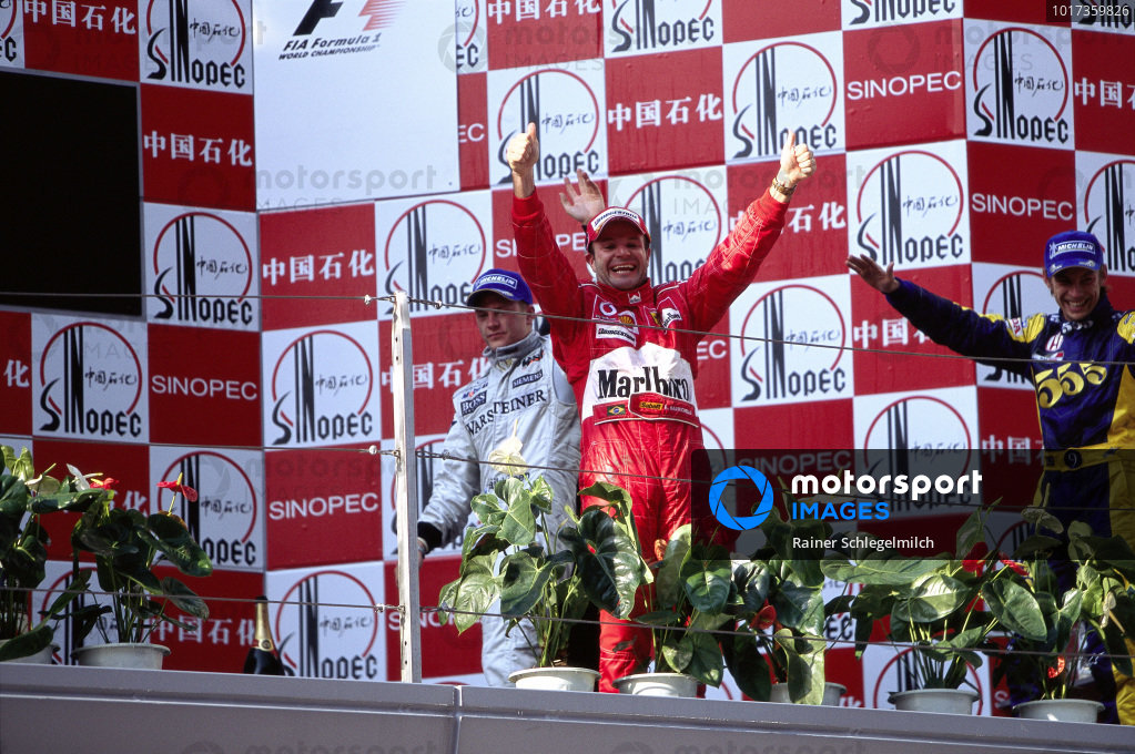 Rubens Barrichello celebrates victory on the podium with Kimi Räikkönen, 3rd position, and Jenson Button, 2nd position.