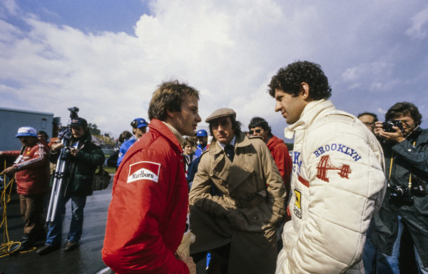 Gilles Villeneuve talks with teammate Jody Scheckter and Jackie Stewart in the pit lane.