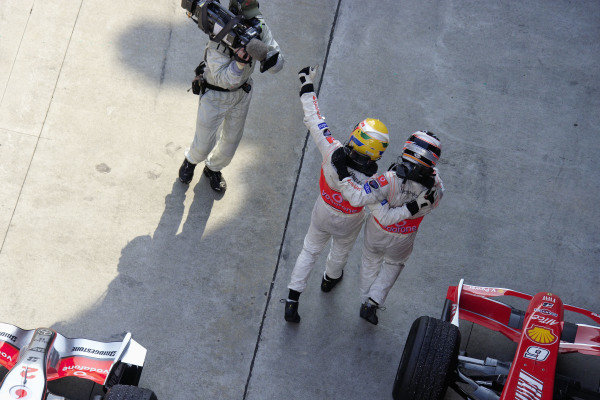 Teammates Fernando Alonso and Lewis Hamilton celebrate their 1-2 result in parc fermé.