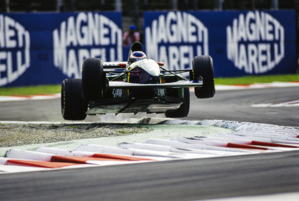 Yannick Dalmas, Larrousse LH94 Ford, gets airborne over the kerbs.