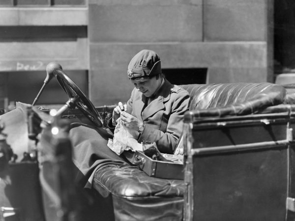 A Women's Legion driver stitches a garment while she waits for her next assignment.