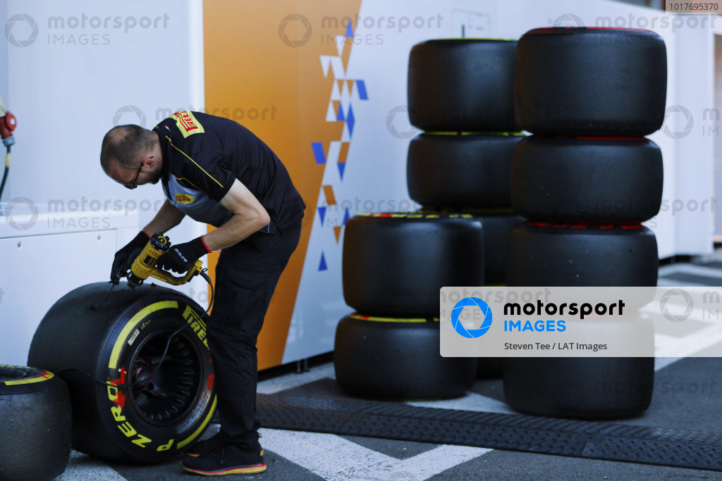 A Pirelli tyre technician at work outside of the McLaren garage