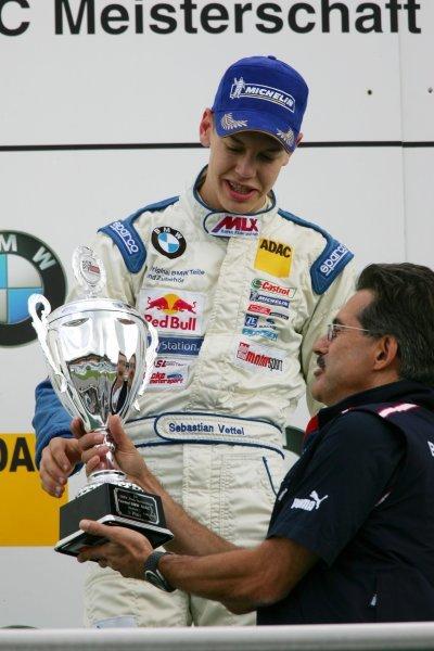 Race 1 winner Sebastian Vettel (GER), ADAC Berlin Brandenburg e.V. (1st), receiving his trophy from Dr. Mario Theissen (GER), BMW Motorsport Director. Formula BMW ADAC Championship, Rd10 race 1, Hockenheimring. 02 October 2004. DIGITAL IMAGE