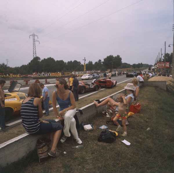 A family sits besides a line of parked cars at Mulsanne Corner during the making of the Steve McQueen film Le Mans. A Porsche 917 of David Piper is in the foreground, behind a Chevron, Lola T170, Porsche 917 and a Matra MS12
