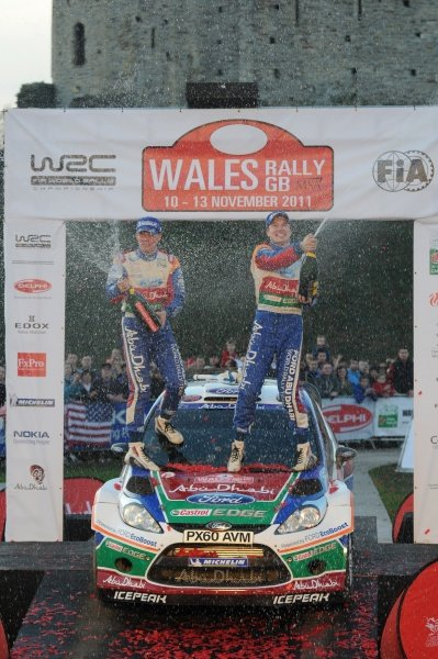 Jari-Matti Latvala (FIN) and Miikka Anttila (FIN) spray the winners' champagne on the podium in Cardiff Castle.