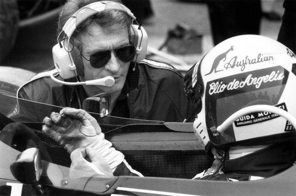 1984 Formula 1 World Championship. Gerard Ducarouge in conversation with Elio de Angelis (Lotus 95T-Renault) in the pits, portrait.  World Copyright: LAT Photographic.  Ref:  B/W Print.