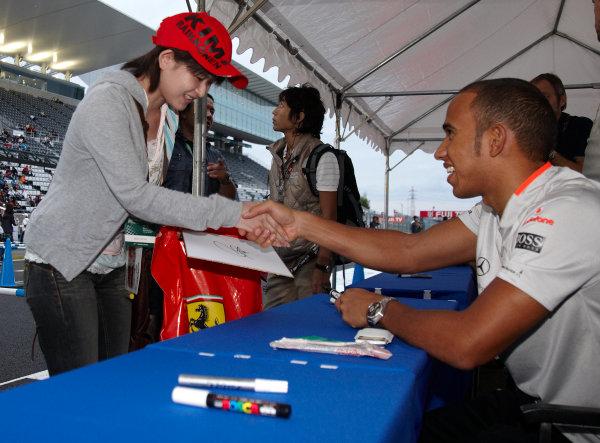Suzuka Circuit, Suzuka, Japan. 1st October 2009. Lewis Hamilton shakes hands with a fan at an autograph signing. Portrait. Atmosphere.  World Copyright: Steve Etherington/LAT Photographic ref: Digital Image SNE29843