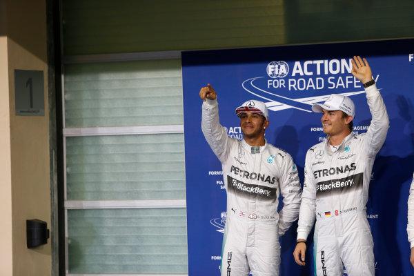 Yas Marina Circuit, Abu Dhabi, United Arab Emirates. Saturday 22 November 2014. Nico Rosberg, Mercedes AMG, and Lewis Hamilton, Mercedes AMG, celebrate in Parc Ferme, after qualifying. World Copyright: Andrew Ferraro/LAT Photographic. ref: Digital Image _FER0569