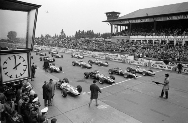 Pole sitter Jim Clark, Lotus 33 Climax waits alongside John Surtees, Cooper T81 Maserati, Jackie Stewart, BRM P261 and Ludovico Scarfiotti, Ferrari 246 on the front row of the grid.