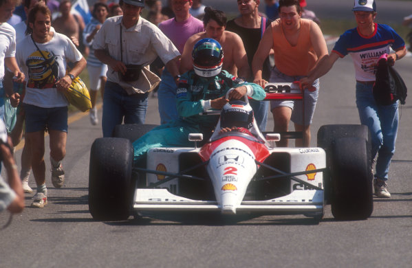 1991 German Grand Prix.Hockenheim, Germany.26-28 July 1991.Gerhard Berger (McLaren MP4/6 Honda) 4th position brings Ivan Capelli (March Ilmor) back to the pits. Fans push back his car after he ran out of fuel after crossing the finish line.Ref-91 GER 06.World Copyright - LAT Photographic