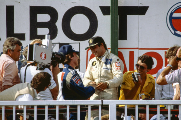 Elio de Angelis, 1st position, and Keke Rosberg, 2nd position, shake hands on the podium.
