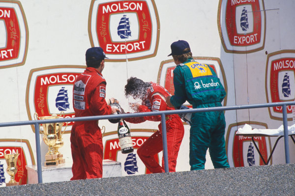 Montreal, Canada. 10th - 12th June 1988. Ayrton Senna (McLaren MP4/4-Honda) 1st position and Thierry Boutsen (Benetton B188-Ford) 3rd position, spray Alain Prost (McLaren MP4/4-Honda), 2nd position, on the podium. Portrait.  World Copyright: LAT Photographic. Ref: 88_CAN_04