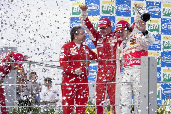 Jean Todt, Kimi Raikkonen and Fernando Alonso stand on the podium in a rain of confetti.