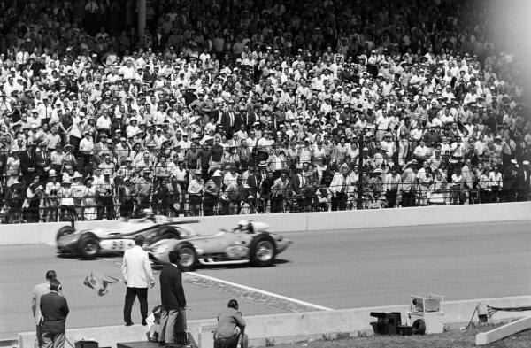 The green flag is waved to signal the start of the race. Parnelli Jones, J. C. Agajanian, Watson Offenhauser, battles with Bobby Unser, Andy Granatelli, Kurtis Novi.