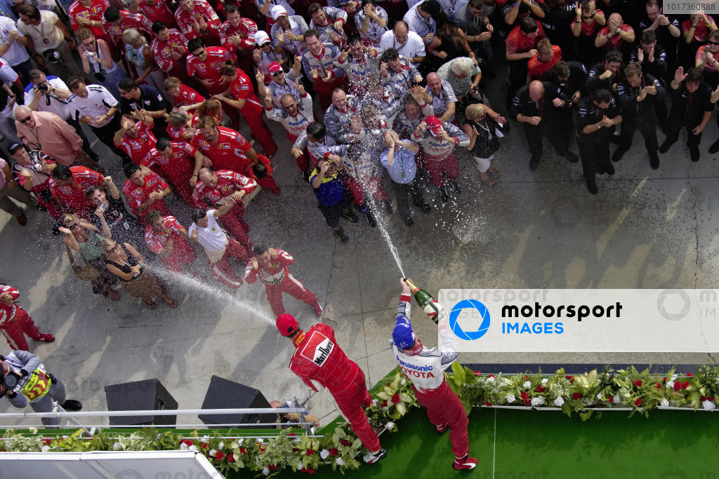 Michael Schumacher, 2nd position, and brother Ralf Schumacher, 3rd position, spray their teams below with champagne.
