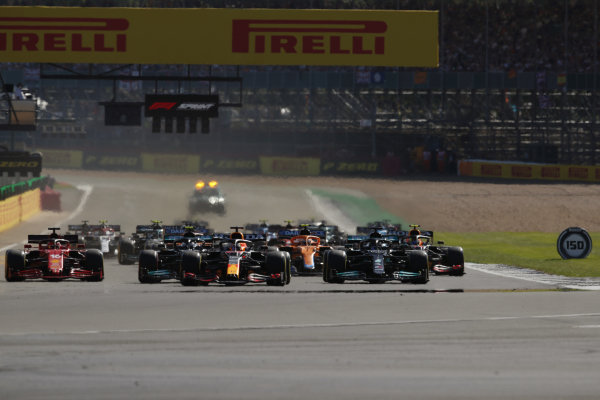 Sir Lewis Hamilton, Mercedes W12, leads Max Verstappen, Red Bull Racing RB16B, Valtteri Bottas, Mercedes W12, Charles Leclerc, Ferrari SF21, and the rest of the field