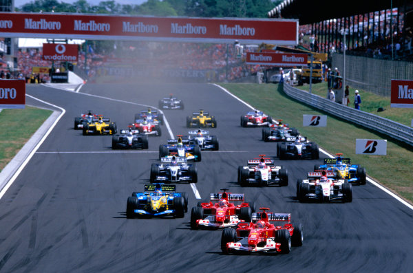 2004 Hungarian Grand Prix Hungaroring, Hungary. 13th - 15th August. Michael Schumacher, Ferrari F2004 leads the field down to the first corner from the start. Action. World Copyright:Charles Coates/LAT Photographic Ref:35mm Image:A02