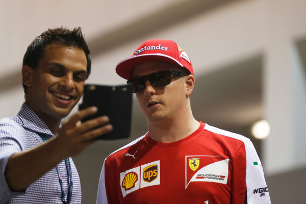 Marina Bay Circuit, Singapore. Friday 18 September 2015. Kimi Raikkonen, Ferrari, poses with a fan for a selfie. World Copyright: Alastair Staley/LAT Photographic ref: Digital Image _R6T4626