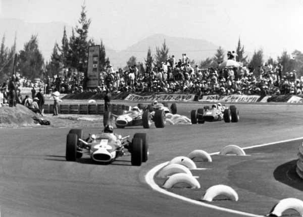 1967 Mexican Grand Prix.Mexico City, Mexico. 22 October 1967.Graham Hill, Lotus 49-Ford, retired, leads Jim Clark, Lotus 49-Ford, 1st position, Chris Amon, Ferrari 312, 9th position, action, and Moises Solana, Lotus 49-Ford, retired, action.World Copyright: LAT PhotographicRef: Motor b&w print