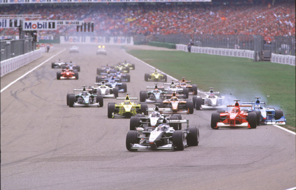 2000 German Grand Prix.Hockenheim, Germany.28-30 July 2000.Mika Hakkinen leads David Coulthard (both McLaren MP4/15 Mercedes) as Michael Schumacher (Ferrari F1-2000) pulls across into Giancarlo Fisichella (Benetton B200 Playlife) on the approach to the Nordkurve at the start, resulting in a crash.World Copyright - Coates/LAT Photographiccrash sequence 03.ref: 35mm A03